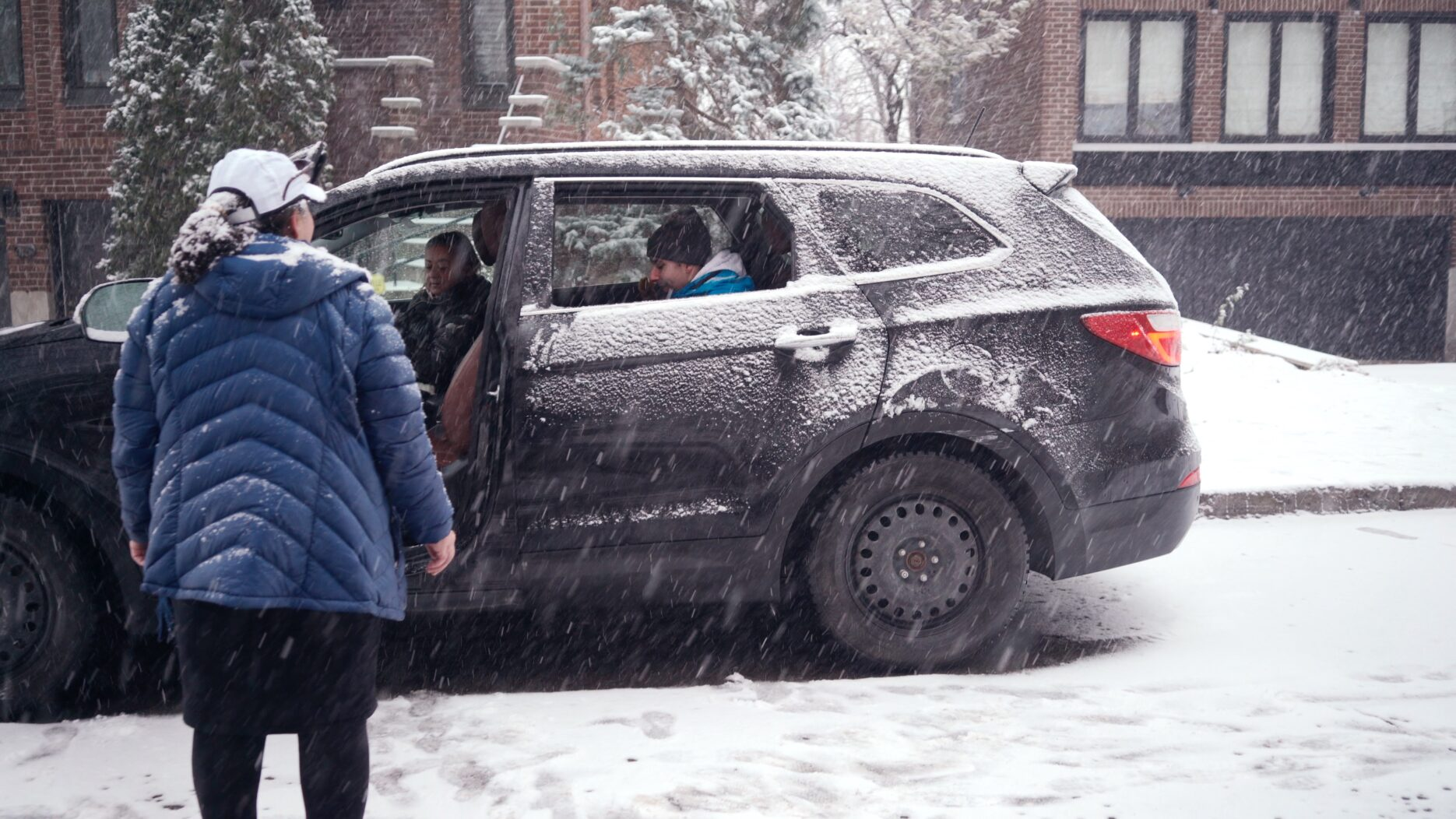 Snowy car with people